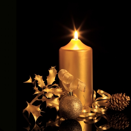 christian candle:  Golden christmas decorations in candlelight including sparkling bauble, ribbon, holly and pine cone, over black background with reflection. Stock Photo
