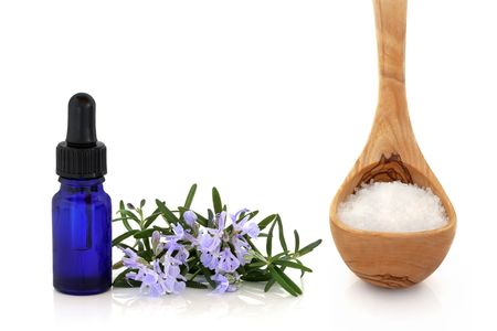 Rosemary herb leaf sprig with flowers and aromatherapy essential oil glass bottle with an olive wood ladle and sea salt, over white background. photo