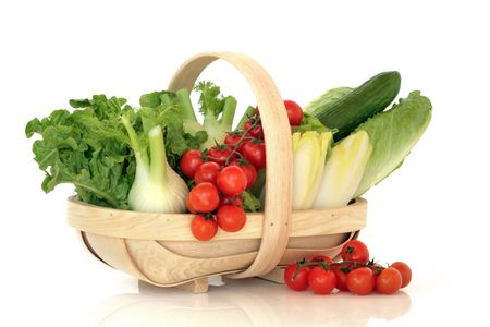 Salad vegetable selection of fennel, chicory, lettuces, cucumber with cherry red tomatoes on the vine in a rustic wooden basket, over white background. photo
