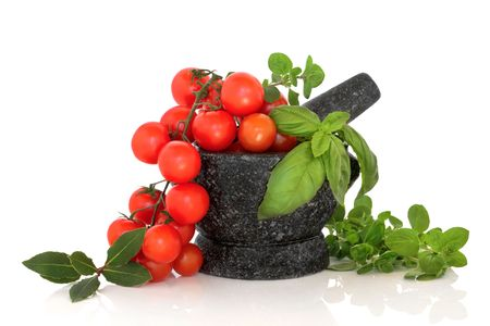Herb leaf selection of oregano, basil and bay leaves with cherry tomatoes  in a granite mortar with pestle, over white background. Stock Photo - 5866674