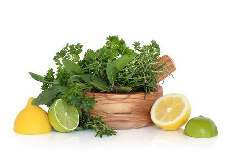 thyme: Lemon and lime fruit met gemengde kruid blad selectie in een olijf hout mortier met stamper, op witte achtergrond.