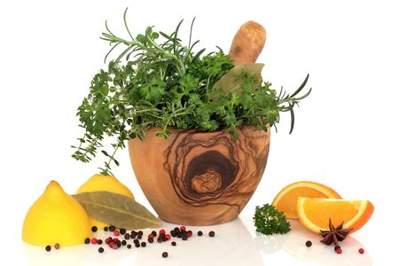 Herb leaf selection of parsley, rosemary and thyme in an olive wood mortar with pestle, lemons, oranges, and spices over white background. photo