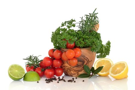 Herb leaves of parsley and rosemary with cherry tomatoes in an olive wood mortar with pestle with lemon and lime fruit halves, bay leaves and peppercorns, over white background. photo
