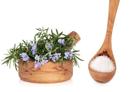 Rosemary herb in flower with leaves  in olive wood mortar with pestle,  with sea salt in a wooden ladle, over white background with reflection.  photo