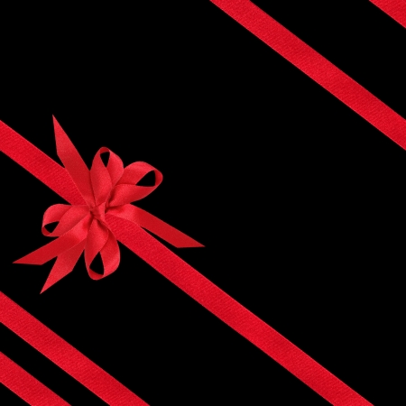 black ribbon bow: Red satin ribbon and bows in an abstract design isolated over black background.