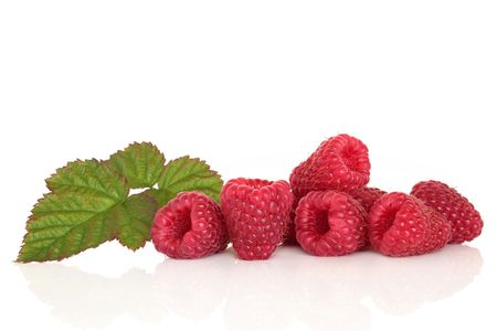 Raspberry fruit with leaf sprig, isolated over white background with reflection.