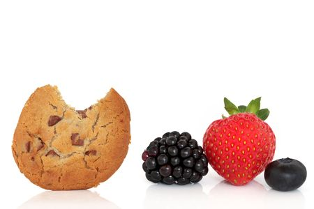 munchy: Chocolate chip cookie with a bite taken out and blackberry, strawberry and blueberry fruit isolated over white background with reflection. Stock Photo