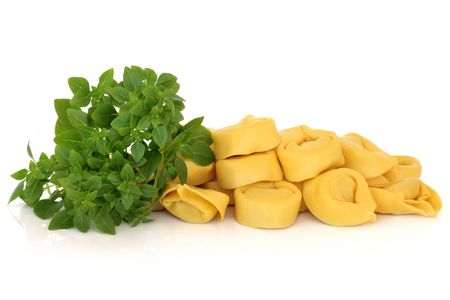 Tortellini pasta with basil herb leaves, isolated over white background with reflection. Stock Photo - 6623149