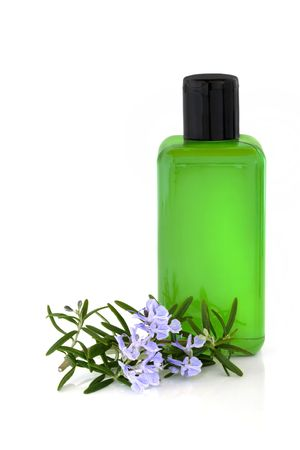 bath essence: Rosemary herb leaf and flower sprig with bath essence in a bottle, isolated over white background. Stock Photo