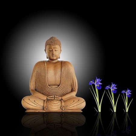 illuminati: Sorridente buddha con gli occhi chiusi in preghiera e blu fiori iride contro uno sfondo nero con bianco bagliore centrale e di riflessione.  Archivio Fotografico