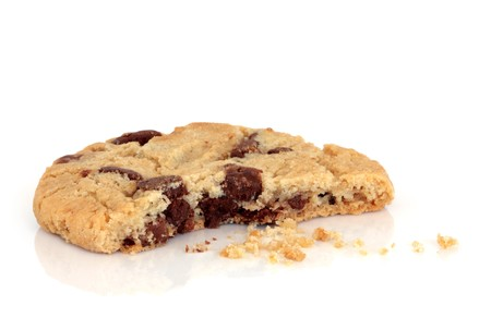 Chocolate chip cookie with a bite taken out and crumbs, isolated over white background. photo