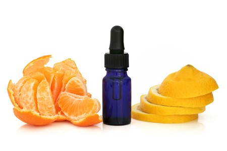 fragrant: Tangerine  peeled and lemon slices with an aromatherapy blue glass essential oil dropper bottle. Isolated over white background. Stock Photo
