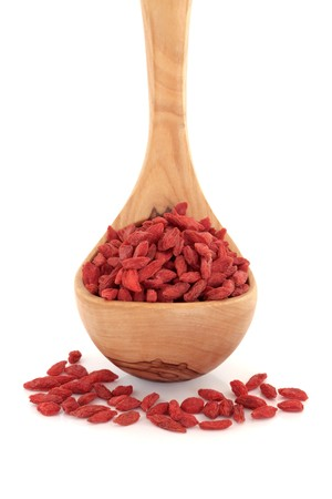 Himalayan goji berry dried fruit in an olive wood ladle and scattered, isolated over white background. Very high in antioxidants. Stock Photo