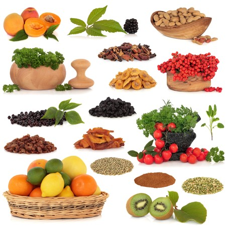 Healthy super food collection of fresh and dried fruit, nuts, herbs, spices, and pulses, very high in antioxidants and vitamins, isolated over white background. photo