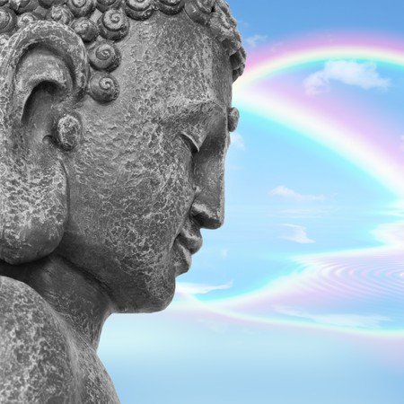 nirvana: Face of a buddha with eyes closed in prayer, with a blue sky and double rainbow in reflection in the distance, symbolising nirvana.  Side view.  Stock Photo