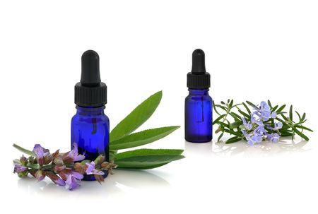 Rosemary and comfrey herb flowers and leaf sprigs with aromatherapy essential oil glass bottles, isolated over white background. photo