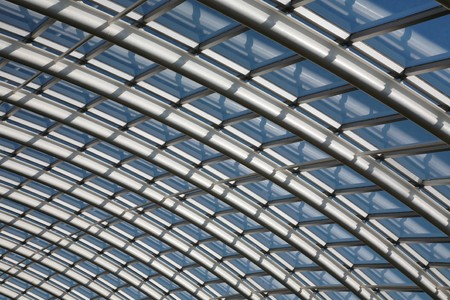 joists: Conservatory roof span with curved metal joists and glass window panes against a blue sky.