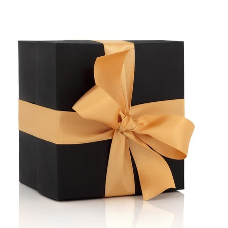 birthday present: Black gift box with gold satin ribbon and large bow, isolated over white background with reflection. Stock Photo