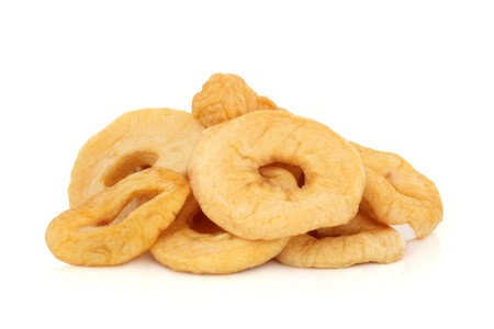 Dried sliced apple rings isolated over white background.