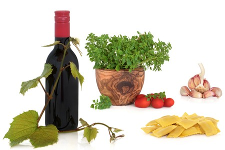 Italian food collection of ravioli pasta, tomatoes and herbs, garlic clove and bottle of red wine with grape leaf sprig, isolated over white background. Stock Photo - 7298920