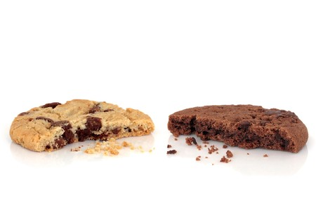 Chocolate chip and all butter cookies with bites taken out of both and scattered crumbs, over white background. Stock Photo