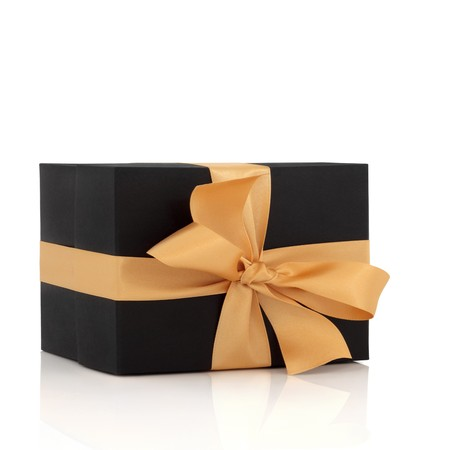 Black gift box with gold satin ribbon and bow, isolated over white background with reflection. Stock Photo - 7400890