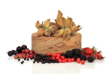 Wild food of autumn of rose hip, elderberry, hawthorn, blackberry, rowan and sloe berry, with  hazelnuts in an olive wood bowl, isolated over white background. photo
