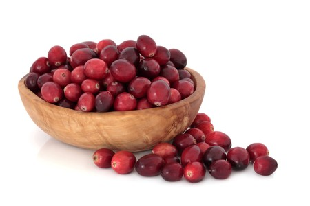 accompagnement: Cranberry fruit in an olive wood bowl and scattered, isolated over white background. Used at christmas and thanksgiving as an accompaniment to turkey.