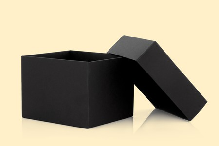 opened: Black cardboard box with the lid off over pastel yellow background with reflection. Stock Photo