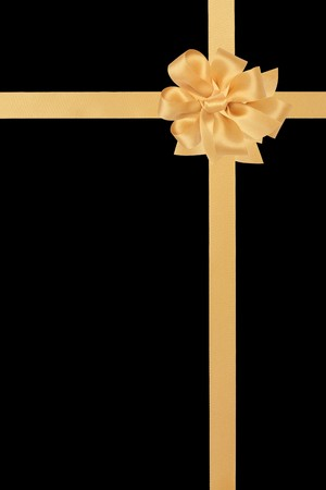black ribbon bow: Gold satin ribbon with bow isolated over black background.