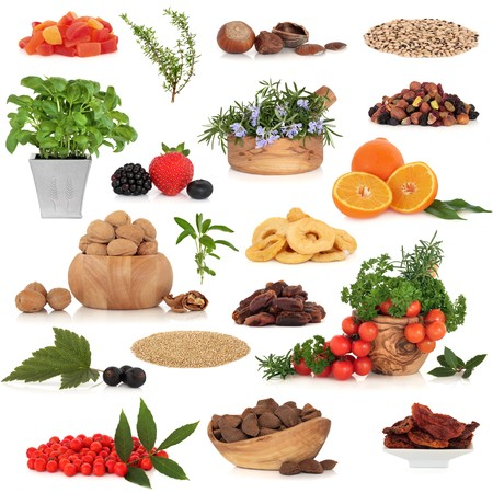 Healthy super food collection of fresh and dried fruit, nuts, herbs, spices, and pluses, very high in antioxidants and vitamins, isolated over white background. photo
