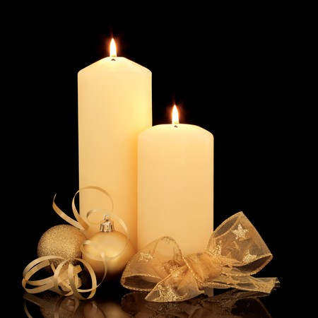 centerpiece: Christmas candle table setting with gold baubles and golden mesh bow and ribbon over black background.