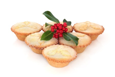 Mince pie group in a triangle formation with holly berry leaf sprig, isolated over white background.
