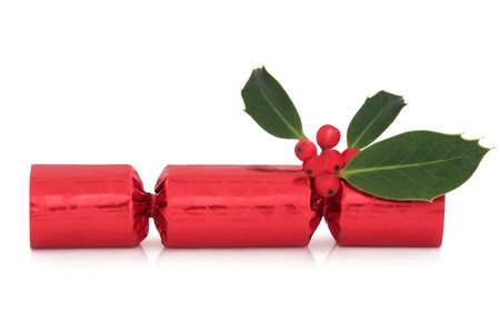 Red christmas cracker with holly berry leaf sprig isolated over white background.