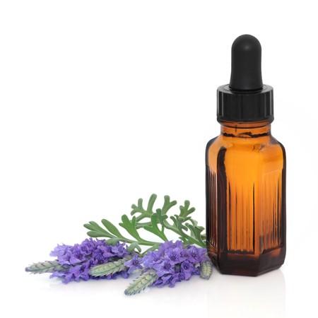 homeopatia: Ramitas de hoja de flor de lavanda de hierba con una botella de gotero de aceite esencial de aromaterapia, aislado sobre fondo blanco.