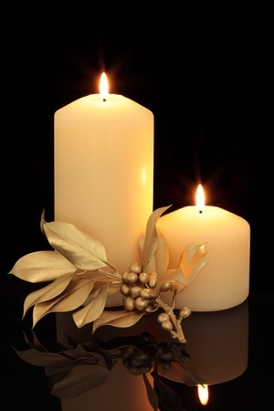 centerpiece: Candle table setting with golden holly berry leaf sprig decoration over black background with reflection. Stock Photo