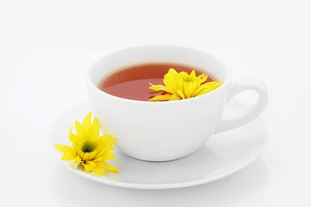 Chrysanthemum tea with flowers in a porcelain tea cup and saucer, isolated over white background. Used in traditional chinese herbal medicine.