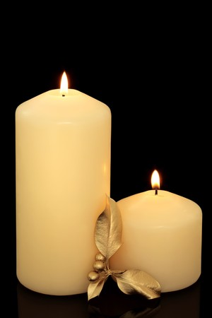 Christmas candles with golden holly berry leaf sprig over black background. photo