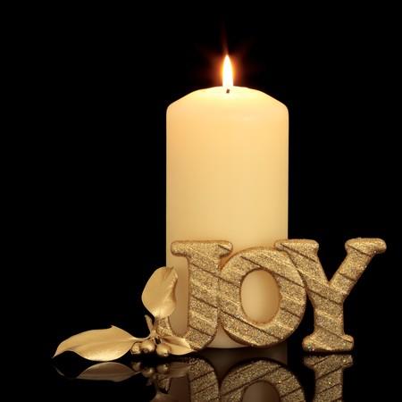 velas de navidad: Configuraci�n de tabla de vela de Navidad con oro glitter alegr�a signo y acebo baya hoja ramita sobre fondo negro con la reflexi�n.  Foto de archivo