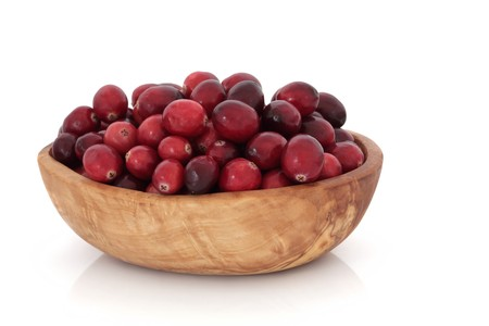 cranberry fruit:  Cranberry fruit in an olive wood bowl, isolated over white background.