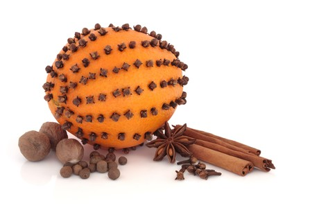 cloves:  Orange fruit with clove spice embedded and cinnamon sticks, nutmeg, star anise, cloves and allspice scattered, isolated over white background. Mulled wine ingredients.