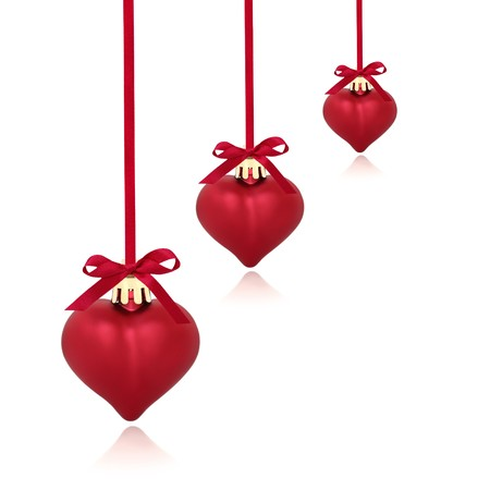 Christmas heart shaped red baubles with ribbon and bows, isolated over white background with copy space.