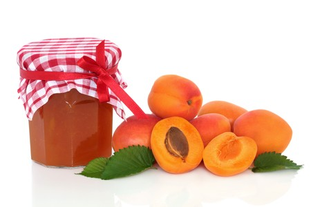 Apricot jam with fruit whole and in half with leaf sprigs, isolated over white background. photo