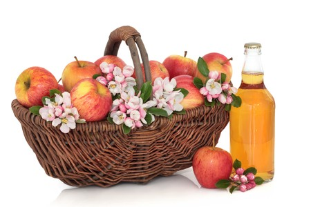 Cider bottle with red apples in a rustic wicker basket with apple flower blossom, isolated over white background. Gala apple variety. photo