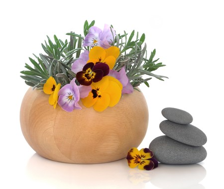 Lavender herb leaf sprigs and yellow viola flowers in a beech wood mortar with pestle with grey spa stones, isolated over white background. Herbs for skincare. photo