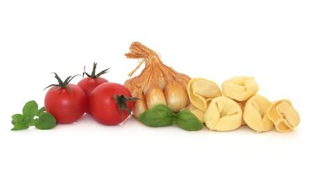 Tortellini pasta, smoked garlic, basil and oregano herb leaf sprigs and tomatoes, isolated over white background. photo