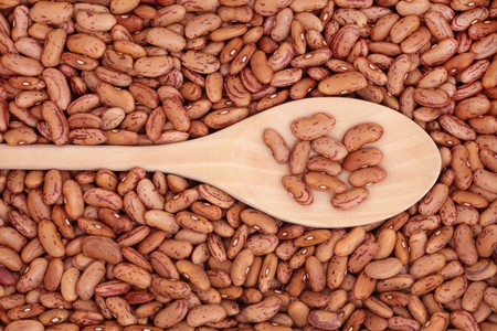 pinto bean: Pinto bean pulses in a wooden spoon and forming a background.