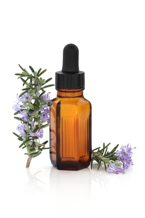 Rosemary herb leaf and flower sprigs with aromatherapy essential oil glass bottle, isolated over white background with reflection. photo