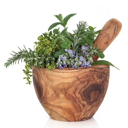 medicinal herbs:  Herb leaf selection of golden thyme, oregano, purple sage, mint and  rosemary in flower in a rustic olive wood mortar with pestle, isolated over white background. Stock Photo