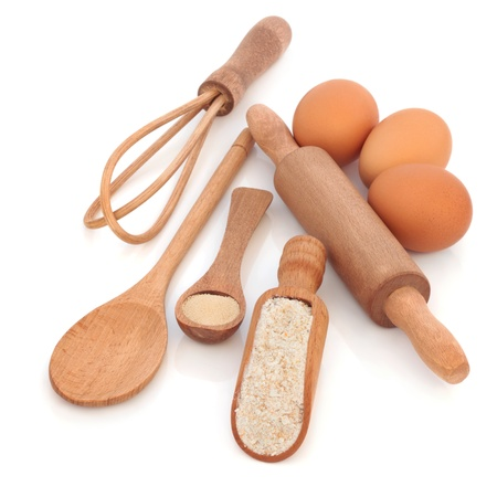 egg whisk:  Baking equipment and ingredients, with wholegrain flour, yeast and eggs, with rustic natural wooden spoons, scoop, whisk and rolling pin, isolated over white background.